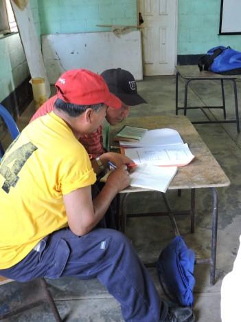 Los actores locales que estan siendo formados e la comunidad estudian los cuadernos que les hemos facilitado