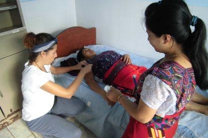 María (Acupuntora Descalza), promotora ayudante en prácticas y mujer de la comunidad recibiendo acupuntura)